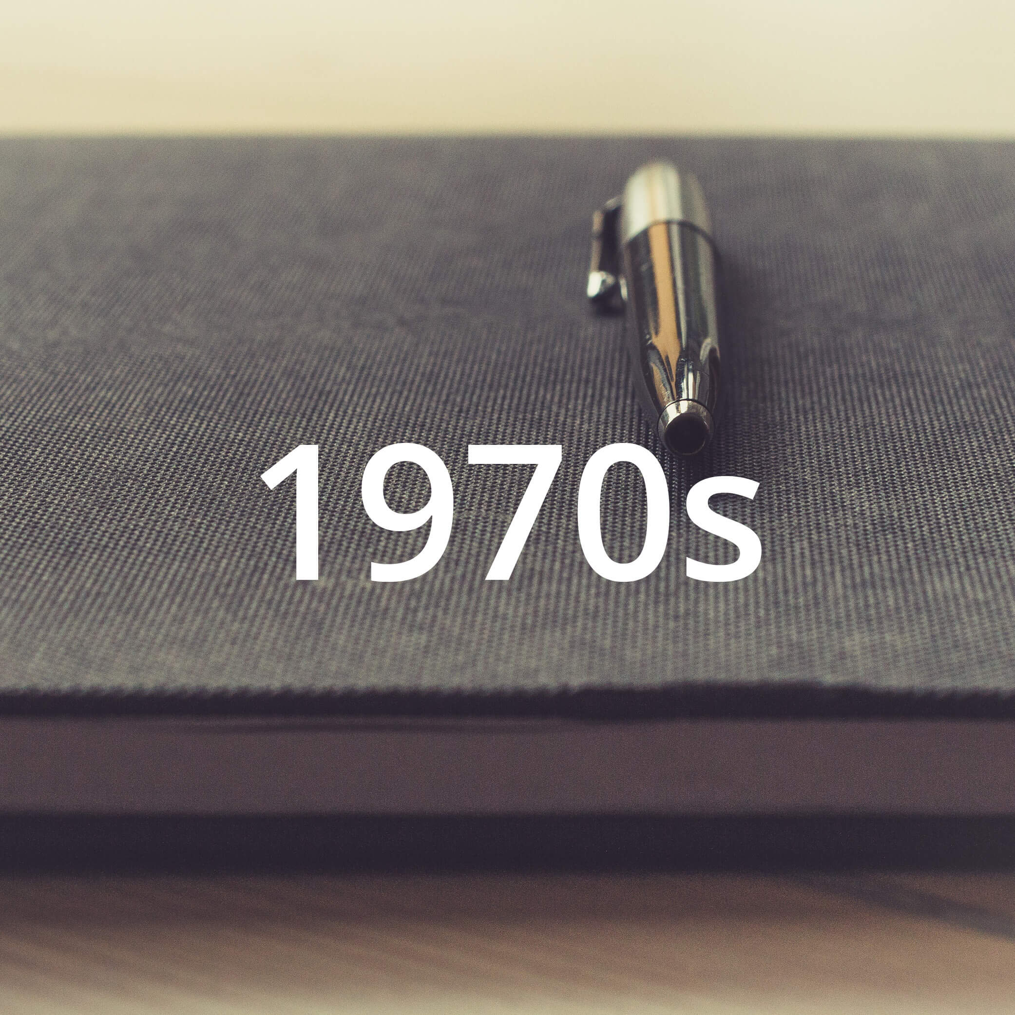 """Photo of a pen laying on a book. Photo also features a text overlay that reads """"1970s""""."""