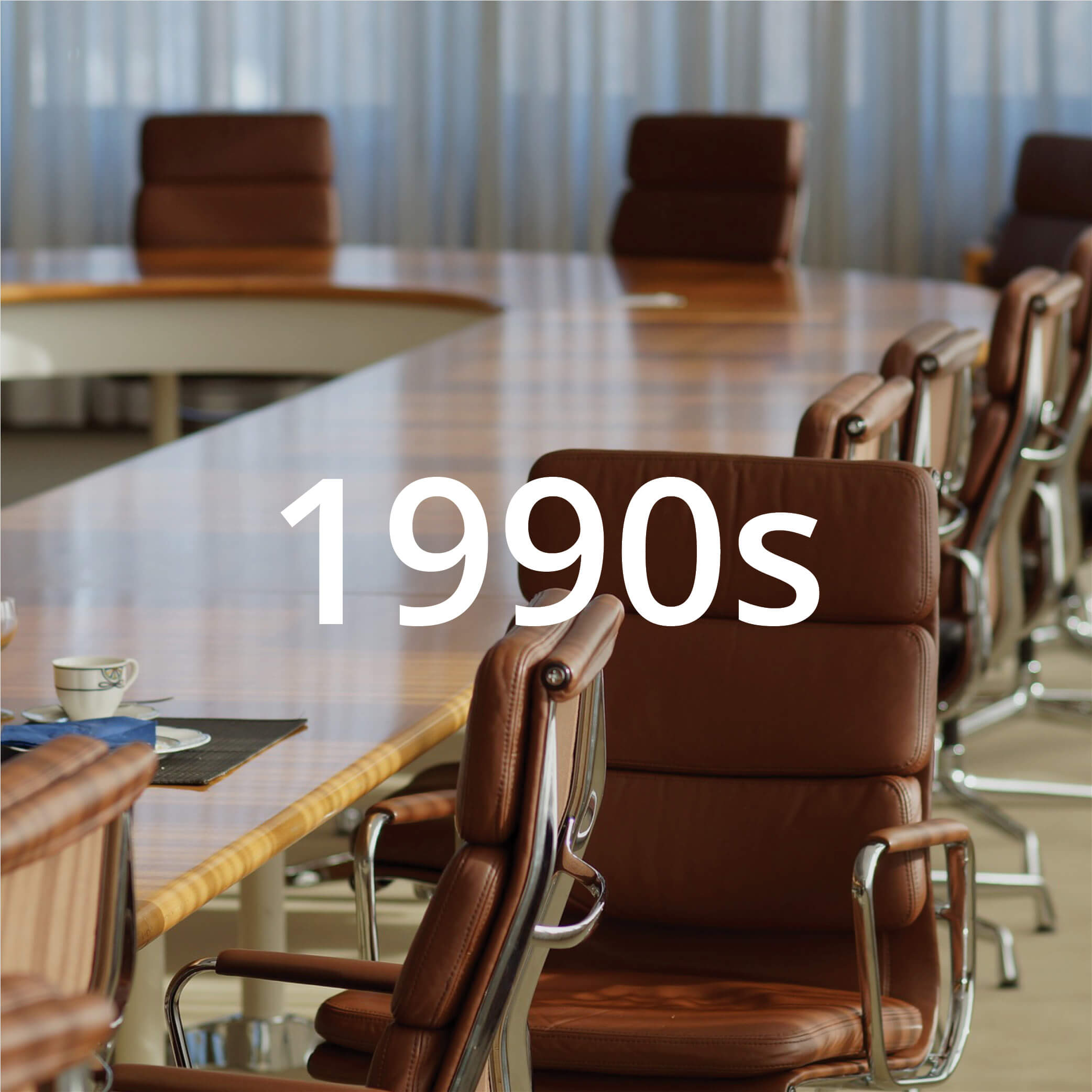 """Photo of a meeting room featuring a u-shaped table and modern brown leather chairs. Photo also features text overlay that reads """"1990s""""."""