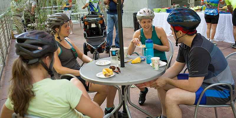 Bicyclists sitting at a table talking